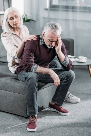 Photo for Senior woman taking care of husband with strong headache at home - Royalty Free Image