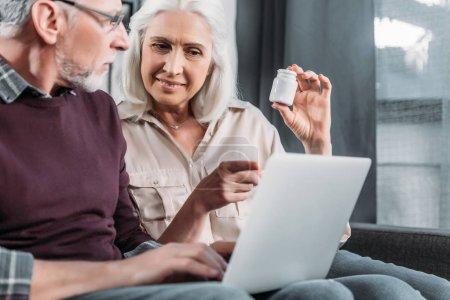 Photo pour Couple de personnes âgées assis sur le canapé et l'achat de médicaments en ligne - image libre de droit