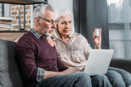 Photo for Senior couple sitting on sofa and buying medicines online - Royalty Free Image
