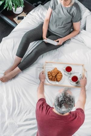 Photo for Overhead view of man brought breakfast in bed while woman using tablet - Royalty Free Image
