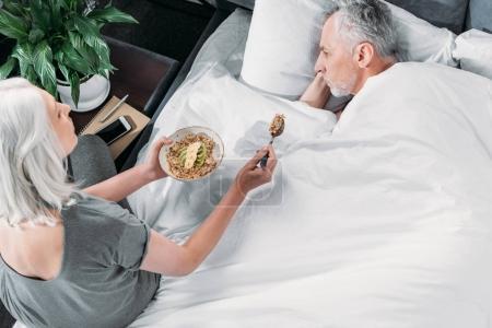 Photo pour Vue de la femme en prenant soin de mari malade dans son lit à la maison - image libre de droit