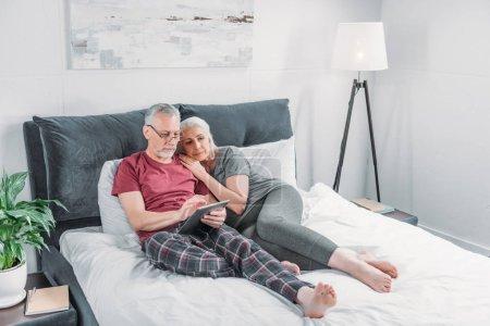 Photo pour Couple sénior avec tablette numérique reposant au lit ensemble - image libre de droit