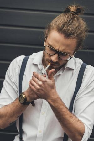 Photo for Close-up handsome stylish man in eyeglasses lighting cigarette with lighter - Royalty Free Image