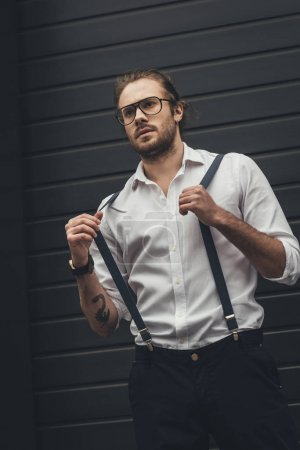Photo for Handsome stylish man in spectacles adjusting suspenders and looking away - Royalty Free Image