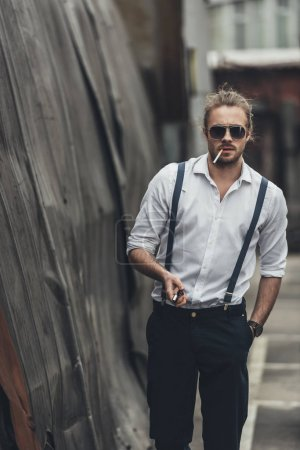 Photo for Stylish young man smoking cigarette and holding lighter while walking with hand in pocket - Royalty Free Image