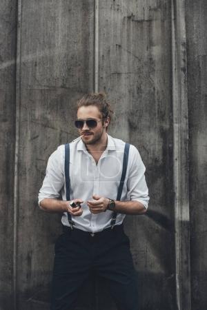 Photo pour Élégant jeune homme confiant fumer cigarette et tenant plus léger - image libre de droit