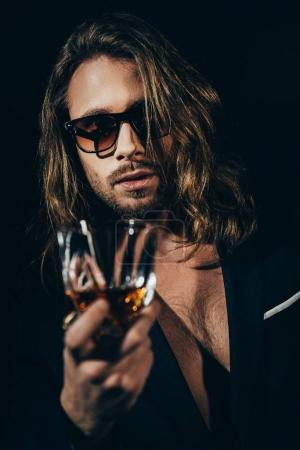 Photo for Handsome bearded long haired man in sunglasses and stylish suit drinking whiskey and looking at camera - Royalty Free Image