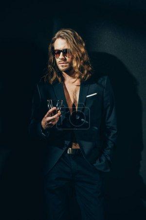 Photo pour Beau barbu homme aux cheveux longs dans des lunettes de soleil et costume élégant tenant verre de whisky sur noir - image libre de droit