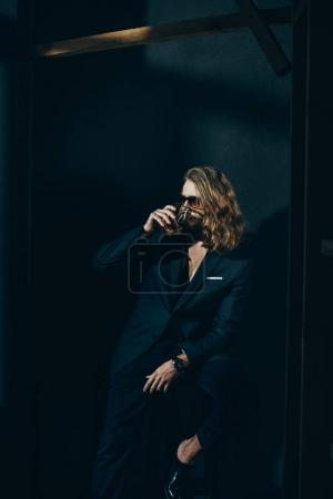 Man in suit drinking whiskey