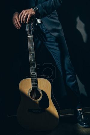 Photo pour Recadrée tir d'homme en costume élégant debout avec une guitare acoustique sur fond noir - image libre de droit