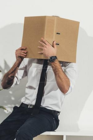 Businessman hiding face with folder