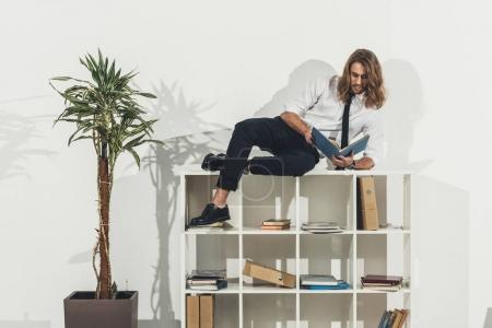 Businessman lying on bookshelf