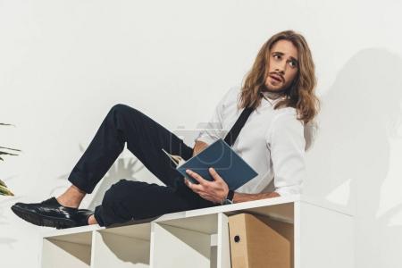Businessman lying on bookshelf