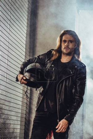 Photo for Stylish long haired bearded man in leather jacket holding helmet and looking at camera - Royalty Free Image