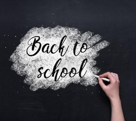 Photo for Cropped shot of hand writing on blackboard with chalk, back to school concept - Royalty Free Image