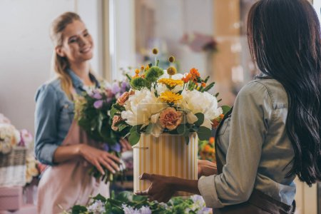 Photo for Attractive young multiethnic florists in aprons working with flowers in flower shop - Royalty Free Image