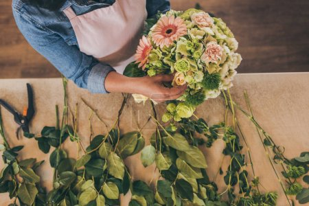 Photo for Close-up partial view of young woman in apron working with bouquet of beautiful fresh flowers - Royalty Free Image