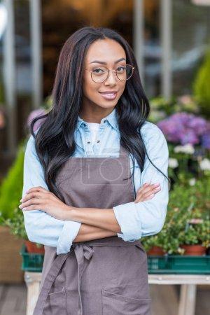 Photo pour Confiant jeune fleuriste afro-américain dans des lunettes debout avec les bras croisés et souriant à la caméra - image libre de droit