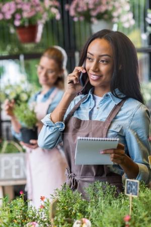 Photo pour Souriant jeune fleuriste afro-américain tenant un carnet et parlant sur smartphone alors que son collègue travaille derrière dans un magasin de fleurs - image libre de droit