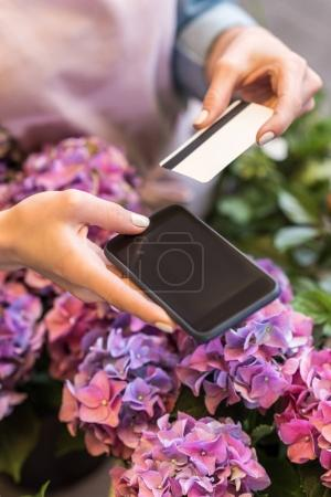 Person with smartphone and credit card