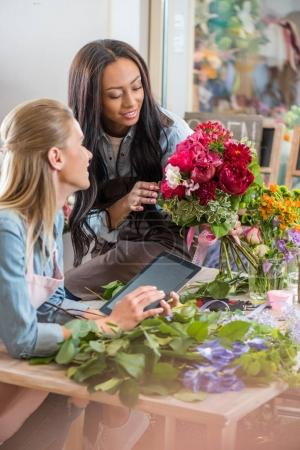 Multiethnic florists with digital tablet and flowers