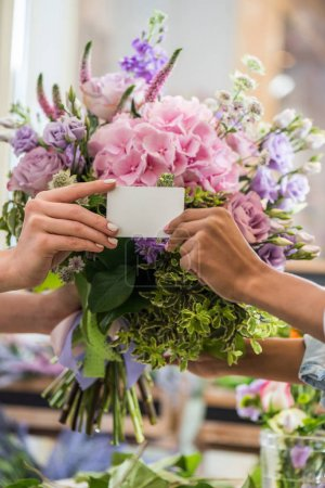 Photo for Close-up partial view of female hands holding blank business card and bouquet of beautiful flowers - Royalty Free Image