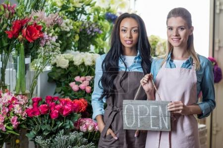 Multiethnic florists with open sign
