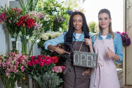 Photo pour Jeunes fleuristes multiethniques pointant vers signe ouvert et montrant pouce levé tout en souriant à la caméra dans le magasin de fleurs - image libre de droit