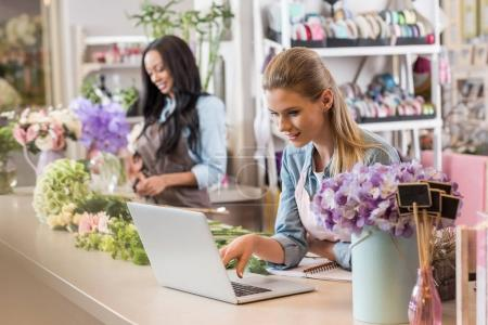 Photo for Young blonde florist using laptop while african american colleague working with flowers behind - Royalty Free Image