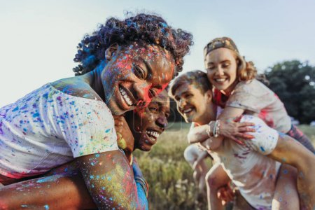 Photo for Happy young multiethnic couples piggybacking at holi festival - Royalty Free Image