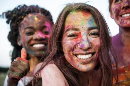 Photo for Happy young multiethnic women with colorful paint on clothes and bodies having fun together at holi festival - Royalty Free Image