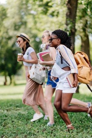 multiethnic girls with books running