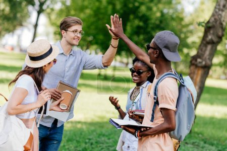 Photo for Cheerful young multiethnic students giving high five while standing together in park - Royalty Free Image
