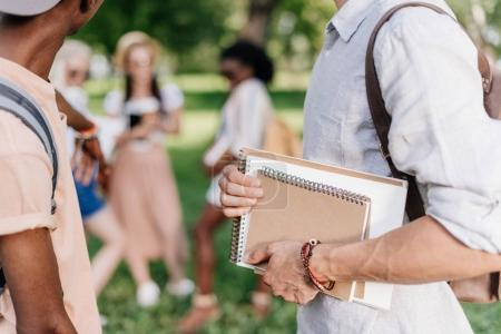 Students with notebooks in park
