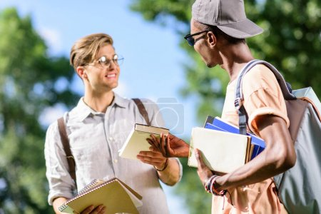 Photo pour Jeunes beaux étudiants multiethniques tenant des livres et se regardant dans le parc - image libre de droit