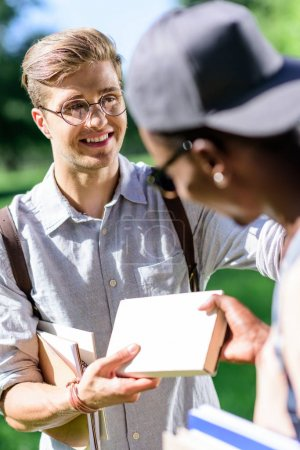 multiethnic students with books in park