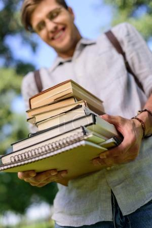 Photo pour Vue rapprochée d'un jeune étudiant souriant tenant une pile de livres - image libre de droit