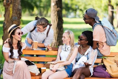 multiethnic students on bench in park