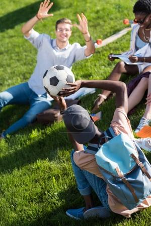 Photo pour Heureux jeunes étudiants multiethniques, jouer avec le ballon alors qu'il étudiait dans le parc - image libre de droit