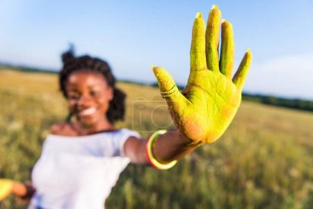 Girl with yellow paint on palm