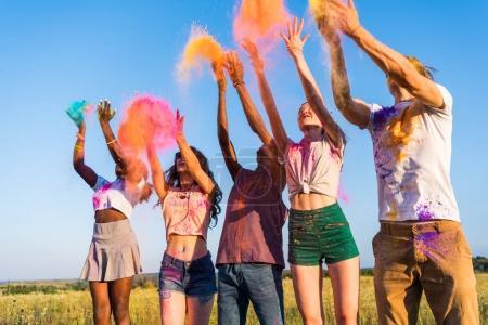 Photo pour Heureux jeunes amis multiethniques jetant de la poudre colorée au festival holi - image libre de droit
