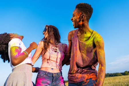 Photo for Cheerful young multiethnic friends with colorful paint on clothes having fun together at holi festival - Royalty Free Image