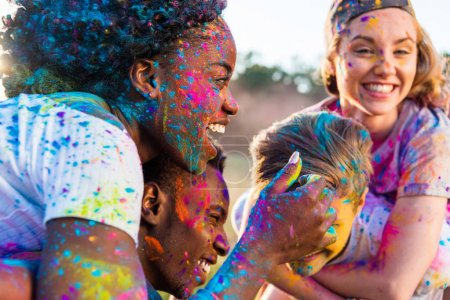 Photo for Happy young multiethnic couples with colorful paint on clothes piggybacking at holi festival - Royalty Free Image