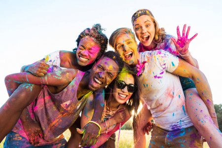 Photo for Happy young multiethnic friends with colorful paint on clothes having fun together at holi festival - Royalty Free Image