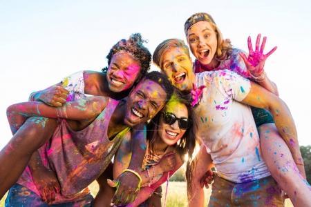 Photo pour Heureux jeunes amis multiethniques avec de la peinture colorée sur les vêtements s'amuser ensemble au festival holi - image libre de droit