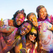 Happy young multiethnic friends with colorful pain...