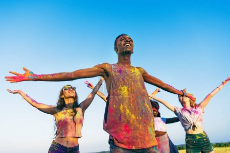 Photo for Happy young multiethnic friends standing with open arms at holi festival of colors - Royalty Free Image