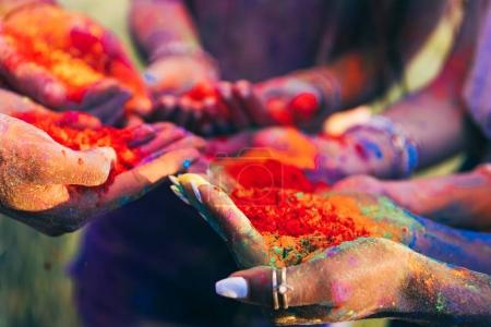 Photo for Close-up partial view of young people holding colorful paint in palms at holi festival - Royalty Free Image