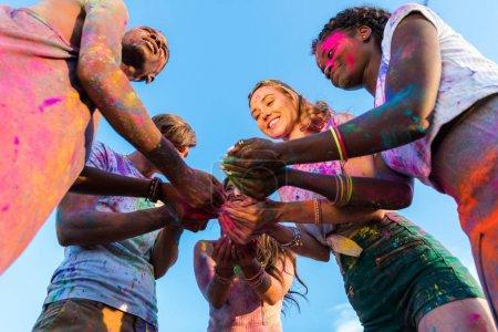 Photo pour Vue à angle bas de jeunes amis multiethniques tenant de la peinture colorée dans les mains au festival holi - image libre de droit