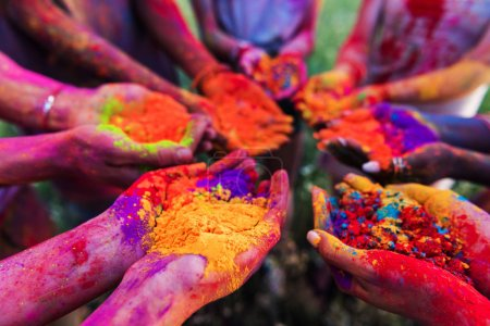 Photo for Close-up partial view of young people holding colorful powder in hands at holi festival - Royalty Free Image